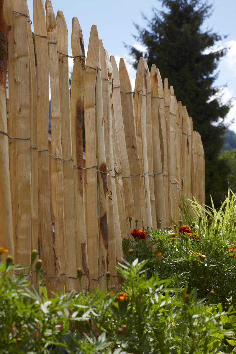 Der französische Staketenzaun aus Kastanienholz ist ein Trendsetter. Mit seinen angespitzten und verdrahteten Hölzern passt er in jeden Garten. Unbehandelt hält der Zaun rund 20 Jahre, ganz ohne Pflege.