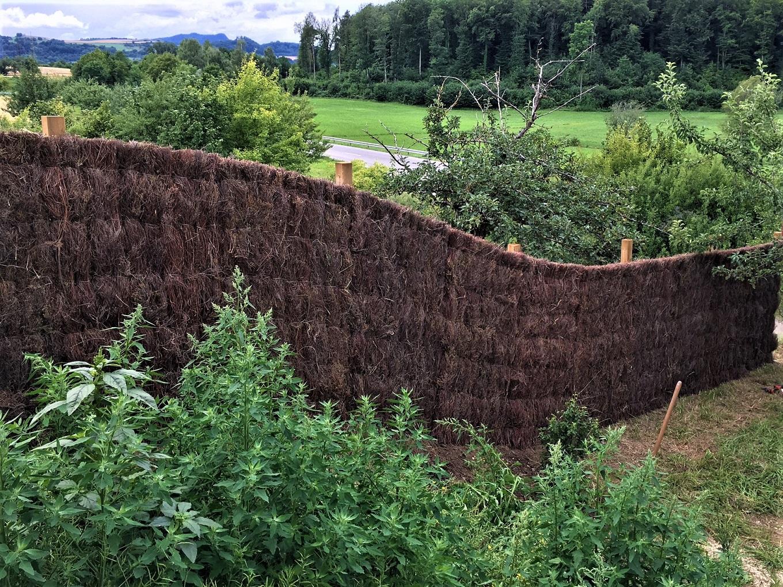 Sichtschutzzaun aus Heidekraut entlang einer langen Grundstücksgrenze